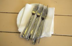 Sur une table en bois un plat Du plat sont les fourchettes et les couteaux de couverts Image stock