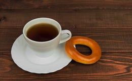 Sur une tasse en bois de table de thé et de biscuit au visage jeune de bagel Image libre de droits