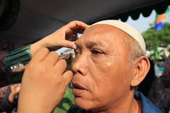 Surabaya indonesia, may 21, 2014. a health worker is checking the patient`s eyes. royalty free stock images