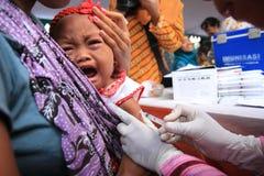 Surabaya Indonésia, pode 21, 2014 um trabalhador do setor da saúde deu vacinações às crianças imagens de stock royalty free