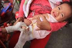 Surabaya Indonésia, pode 21, 2014 um trabalhador do setor da saúde está dando tiros da imunização a uma criança foto de stock royalty free
