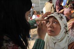 Surabaya Indonésia, pode 21, 2014 um trabalhador do setor da saúde está verificando os olhos do paciente imagens de stock royalty free