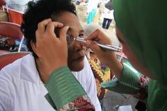 Surabaya Indonésia, pode 21, 2014 um trabalhador do setor da saúde está verificando os olhos do paciente fotografia de stock