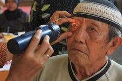 Surabaya Indonésia, pode 21, 2014 um trabalhador do setor da saúde está verificando os olhos do paciente imagem de stock
