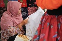 Surabaya Indonesië 20 augustus, 2015 Een vrouw maakt een batikmotief gebruikend het afschuinen stock afbeelding