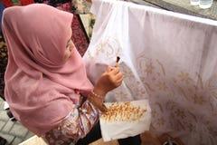 Surabaya Indonesië 20 augustus, 2015 Een vrouw maakt een batikmotief gebruikend het afschuinen stock foto