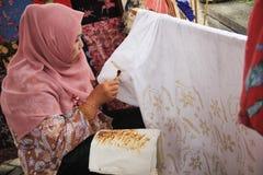 Surabaya Indonesia 20 de agosto de 2015 Una mujer hace un adorno del batik usando el biselaje imagenes de archivo