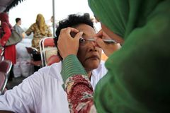 Surabaya indonesia, may 21, 201surabaya indonesia, may 21, 2014. a health worker is being check the patient`s eye health. Surabaya indonesia, may 21, 2014. a stock image