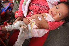 Surabaya indonesia, may 21, 2014. a health worker is giving immunization shots to a child. royalty free stock photo