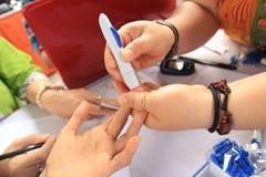 Surabaya Indonesia, puede 21, 2014 un ayudante de sanidad está comprobando la sangre de un paciente imagen de archivo libre de regalías