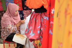 Surabaya Indonesien Augusti 20, 2015 En kvinna gör ett batikmotiv genom att använda att välta royaltyfri fotografi