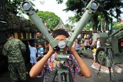Surabaya-Indonesien December 10, 2014 Ett barn försöker kikare för arméstridutrustning på en utställning av hjälpmedel och utrust fotografering för bildbyråer