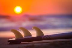 Surboard auf Strand bei Sonnenuntergang oder Sonnenaufgang Lizenzfreies Stockbild