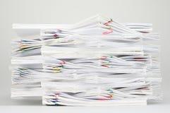 Surchargez le document avec le trombone coloré sur la table blanche Photographie stock libre de droits