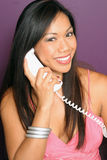 Sure we can help you with that. Worker smiles as she hears your needs on the phone Royalty Free Stock Photography
