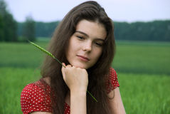 Sure girl in red dress in green wheat field Royalty Free Stock Images