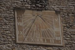 Sure a stone facade of a house, a sundial. The numbers are in roman letters the dial is brown Stock Image