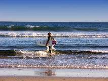 Into The Surf. Young man ready to surf at Malibu, California Royalty Free Stock Images