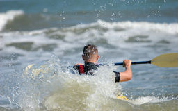 Into the surf 2. Back view of a man kayaking in ocean surf Royalty Free Stock Photo