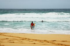 Surf. Young boy going on the beach with a surf board Royalty Free Stock Photography