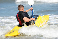 Into the surf. Man kayaking in ocean surf stock photo