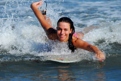 Surf babe!. Beautiful model paddles on her surf board Stock Images