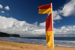 Surf beach. Cloudy surf beach and red-yellow flag Royalty Free Stock Image