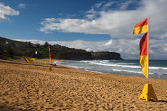 Surf beach. Sunny surf beach and red-yellow flags Royalty Free Stock Photo