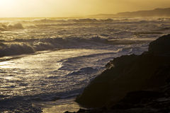 Surf on beach at sunset. Roiling surf and waves at an ocean beach at sunset Stock Photo