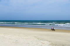 Surf Bikers. Two friends bike up the coast as the surf crashes onto the shore Royalty Free Stock Photo