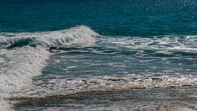 The surf of the blue turquoise sea with white perpendicular wave. S on the sandy beach. Kassandra,  Chalkidiki, Greece Royalty Free Stock Photography