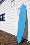 Surf board. A blue surf board against a white wall stock photography
