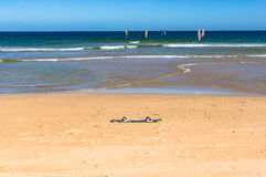 Surf board on the sand with surfers on waves at the distance Royalty Free Stock Photo