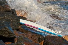 Surf board stranded and stuck on the rocks. Surf board stranded on the rocks and rough sea in the background royalty free stock photos
