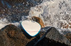 Surf board stuck and stranded. On the rocks and rough sea royalty free stock photo