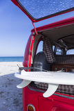Surf board in a van. Detail of a surfboard in a luggage compartment of a classic van on a surf session on the beach - focus on the board Stock Image