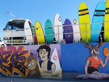 Surf boards and an old van by graffiti painted wall stock photo