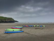 Surf boards ready to go. Colorful surfboards placed on a beach for rental awaiting surfers. Stormy clouds and sea in the back ground stock images