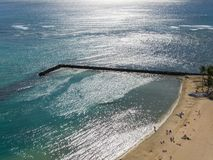 Surf Break on Waikiki. Jetty on a Waikiki beach with sunlight sparkles reflected in the water Stock Photography