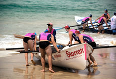 Surf carnival. Rowing team taking start position at surf carnival on Mollymook Beach, South Coast, NSW, Australia - November 2013 Stock Photo