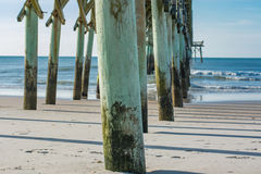 Surf City pier at the beach in North Carolina. View of the pier from the sandy shore.  Green hues mark the posts and blue skies fill the horizon Royalty Free Stock Photo