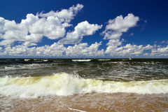 Surf and Cumulus clouds. Beautiful storm Baltic sea in Sunny summer's day Royalty Free Stock Images