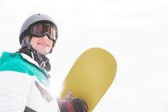 Surf des neiges de sourire de participation de jeune homme contre le ciel clair Images libres de droits