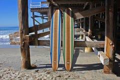Surf di legno contro il pilastro della spiaggia di California Fotografia Stock Libera da Diritti