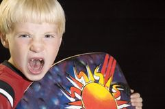 Surf Dude. A toothless youth roars while holding a boogie board Stock Photos