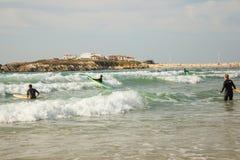 Surf'in em Baleal durante uma maré áspera com a vila pequena de Baleal no horizonte foto de stock royalty free