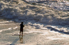 Surf Fisherman. A Silhouetted man surf fishing stock photo