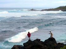 Surf Fishing. Two male tourists fishing in the heavy surf on a northshore beach of Maui, Hawaii Stock Photos