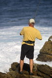 Surf fishing. Man fishing off the rocks Royalty Free Stock Images