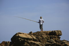 Surf fishing. Man fishing off the rocks Royalty Free Stock Photo
